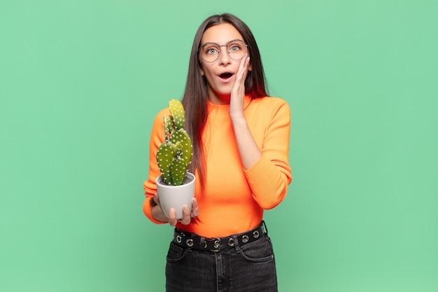 Jeune jolie femme se sentant choquée et effrayée, l'air terrifiée avec la bouche ouverte et les mains sur les joues. concept de cactus