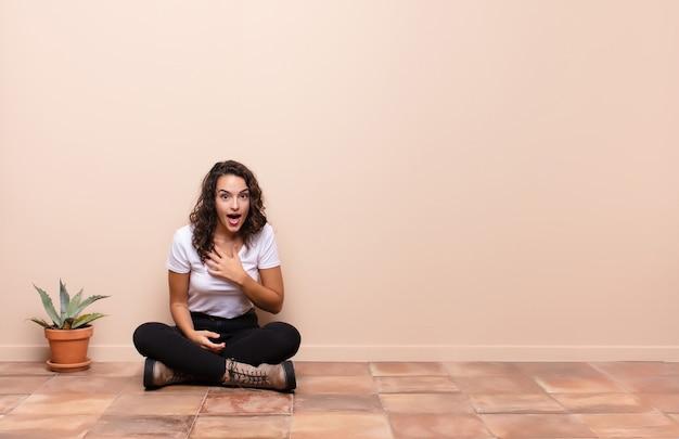 Jeune jolie femme se sentant choquée et surprise, souriante, prenant la main à coeur, heureuse d'être celle ou montrant sa gratitude assis sur un sol en terrasse