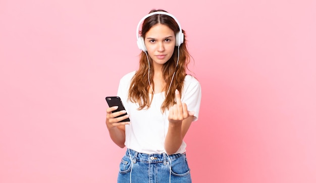 Jeune jolie femme se sentant en colère, agacée, rebelle et agressive avec des écouteurs et un smartphone
