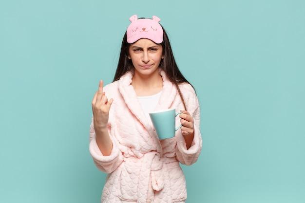 Jeune jolie femme se sentant en colère, agacée, rebelle et agressive, renversant le majeur, ripostant. concept de réveil en pyjama