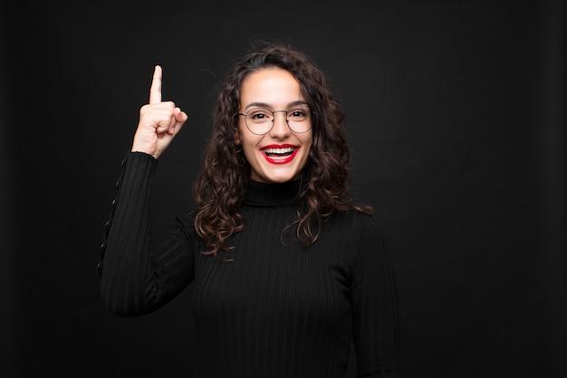 Jeune jolie femme se sentant comme un génie heureux et excité après avoir réalisé une idée, levant joyeusement le doigt, eureka! contre le mur noir.