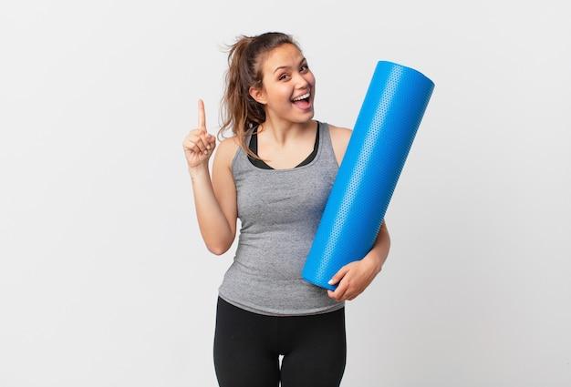 Jeune jolie femme se sentant comme un génie heureux et excité après avoir réalisé une idée et tenant un tapis de yoga