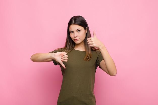 Jeune jolie femme se sentant confuse, désemparée et incertaine, pondérant le bon et le mauvais dans différentes options ou choix contre le mur rose