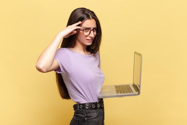 Jeune jolie femme se sentant confuse et perplexe, montrant que vous êtes fou, fou ou fou. concept d'ordinateur portable