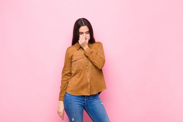Jeune jolie femme se sentant dégoûtée, tenant le nez pour éviter de sentir une odeur nauséabonde et désagréable contre le mur rose