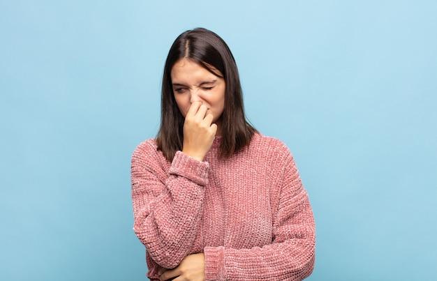 Jeune jolie femme se sentant dégoûtée, tenant le nez pour éviter de sentir une odeur nauséabonde et désagréable