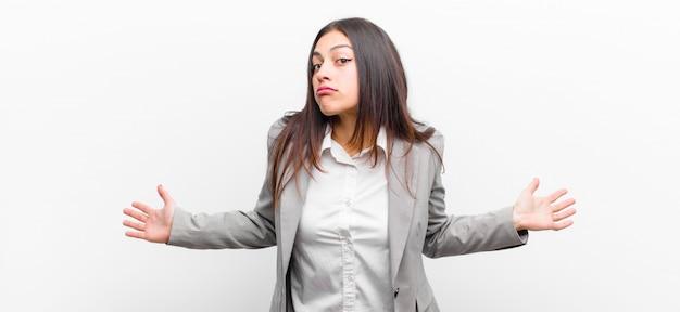 Jeune jolie femme se sentant désemparée et confuse, n'ayant aucune idée, absolument perplexe avec un regard idiot ou stupide isolé contre un mur blanc
