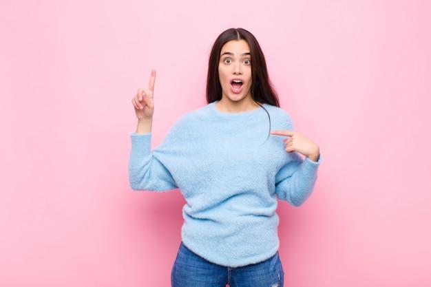 Jeune jolie femme se sentant fière et surprise, pointant vers soi en toute confiance, se sentant comme le numéro un contre le mur rose