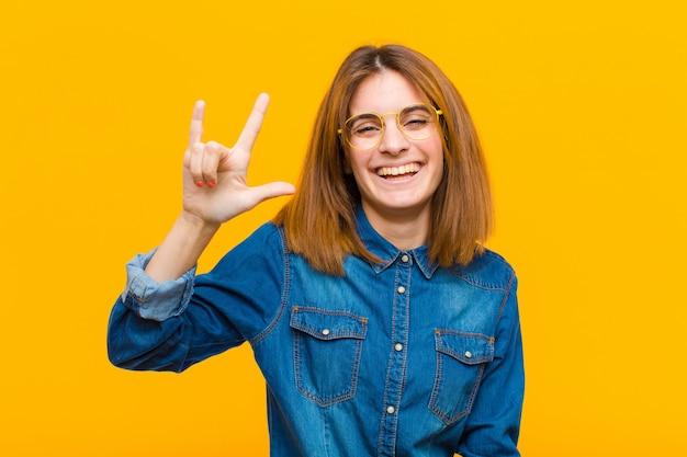 Jeune jolie femme se sentant heureuse, amusante, confiante, positive et rebelle, faisant du rock ou du heavy metal signe avec la main contre le jaune