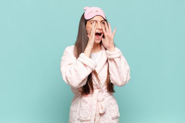 Jeune jolie femme se sentant heureuse, excitée et positive, donnant un grand cri avec les mains à côté de la bouche, appelant. concept de réveil en pyjama