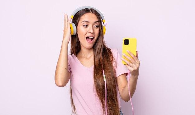 Jeune jolie femme se sentant heureuse, excitée et surprise. casque et smartphone