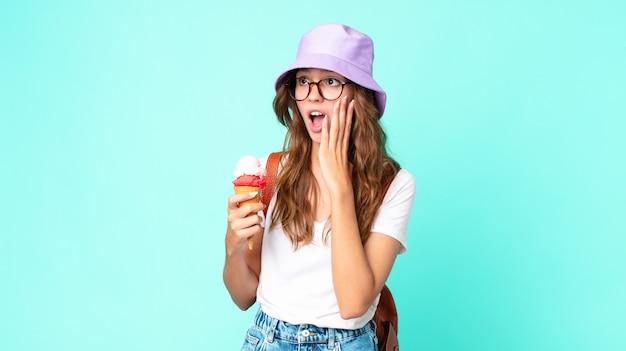 Jeune jolie femme se sentant heureuse, excitée et surprise tenant une glace. concept d'été