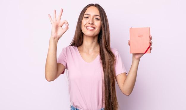 Jeune jolie femme se sentant heureuse, montrant son approbation avec un geste correct. concept de planificateur 2022