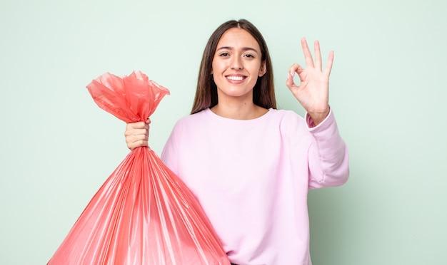 Jeune jolie femme se sentant heureuse, montrant son approbation avec un geste correct. notion de poubelle
