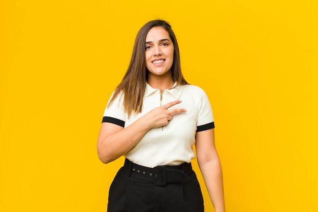Jeune jolie femme se sentant heureuse, positive et réussie, avec la main en forme de v sur la poitrine, montrant la victoire ou la paix sur le mur orange