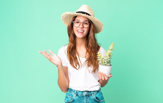 Jeune jolie femme se sentant heureuse, surprise de réaliser une solution ou une idée avec un chapeau de paille et tenant un cactus