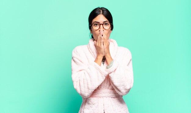 Jeune jolie femme se sentant inquiète, bouleversée et effrayée, couvrant la bouche avec les mains, regardant anxieuse et ayant foiré. concept de pyjama