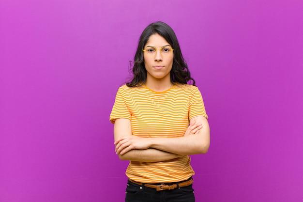 Jeune jolie femme se sentant mécontente et déçue, l'air sérieuse, agacée et en colère avec les bras croisés contre le mur violet