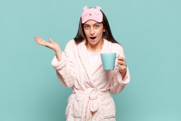 Jeune jolie femme se sentant perplexe et confuse, doutant, pondérant ou choisissant différentes options avec une expression amusante. concept de réveil en pyjama