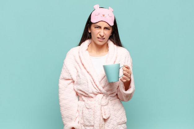 Jeune jolie femme se sentant perplexe et confuse, avec une expression stupide et abasourdie en regardant quelque chose d'inattendu. concept de réveil en pyjama