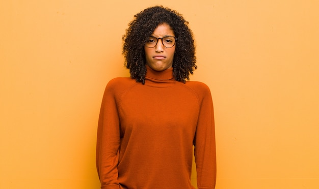 Jeune jolie femme se sentant perplexe et confuse, avec une expression stupide et stupéfaite en regardant quelque chose d'inattendu contre le mur orange