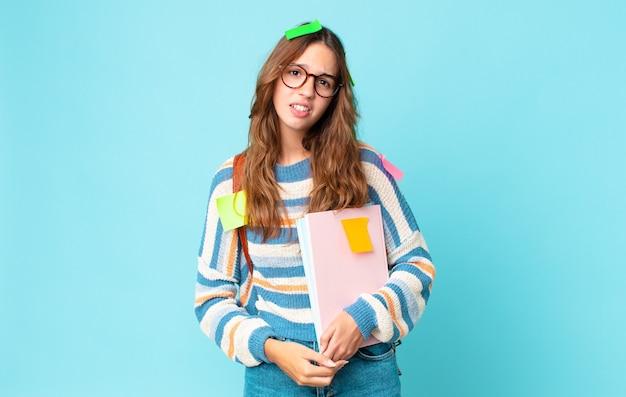Jeune jolie femme se sentant perplexe et confuse avec un sac et tenant des livres