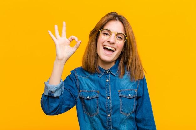 Jeune jolie femme se sentant réussie et satisfaite, souriant avec la bouche grande ouverte, faisant signe avec la main contre le mur jaune