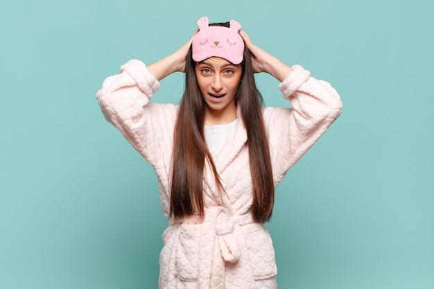Jeune jolie femme se sentant stressée, inquiète, anxieuse ou effrayée, les mains sur la tête, paniquée par erreur. concept de réveil en pyjama