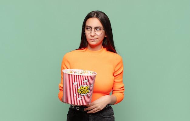 Jeune jolie femme se sentant triste, bouleversée ou en colère et regardant de côté avec une attitude négative, fronçant les sourcils en désaccord. concept de pop corn