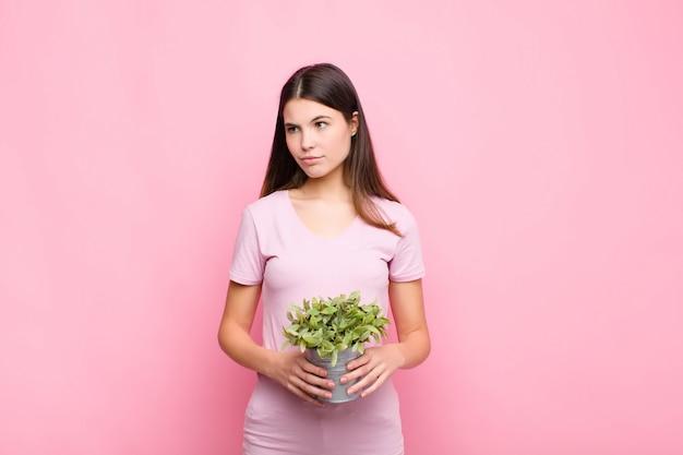Jeune jolie femme se sentant triste, bouleversée ou en colère et regardant de côté avec une attitude négative, fronçant les sourcils en désaccord avec une plante