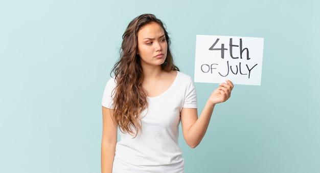 Jeune jolie femme se sentant triste, contrariée ou en colère et regardant vers le concept de la fête de l'indépendance