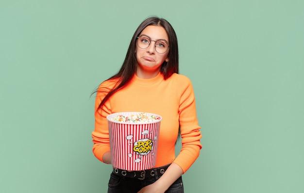 Jeune jolie femme se sentant triste et pleurnicharde avec un regard malheureux, pleurant avec une attitude négative et frustrée. concept de pop corn