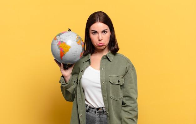 Jeune jolie femme se sentant triste et pleurnicharde avec un regard malheureux, tenant un globe terrestre