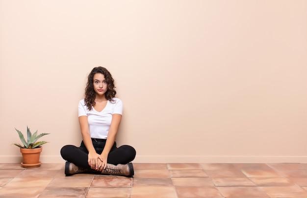 Jeune jolie femme se sentant triste et stressée, bouleversée par une mauvaise surprise, avec un regard négatif et anxieux assis sur le sol d'une terrasse