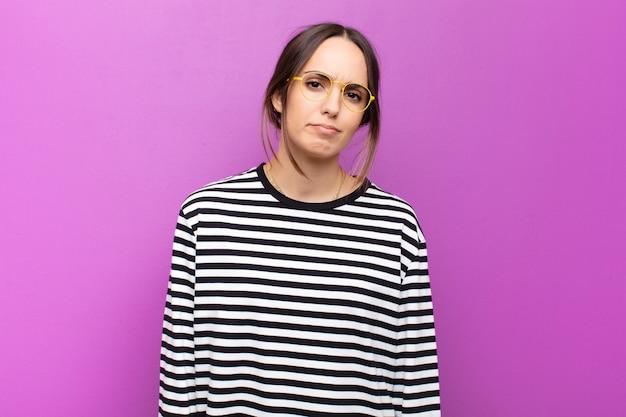 Jeune jolie femme se sentant triste et stressée, bouleversée par une mauvaise surprise, avec un regard négatif et anxieux sur le mur violet