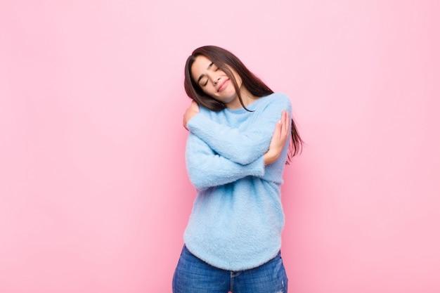 Jeune jolie femme se sentir amoureux, souriant, câlins et se serrant dans ses bras, rester célibataire, être égoïste et égocentrique contre le mur rose