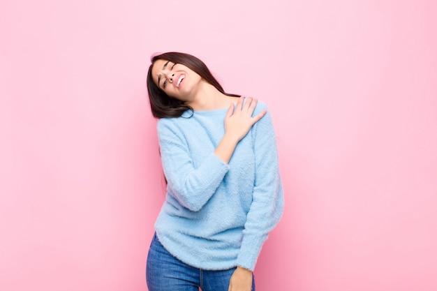 Jeune jolie femme se sentir fatiguée, stressée, anxieuse, frustrée et déprimée, souffrant de douleurs au dos ou au cou contre le mur rose