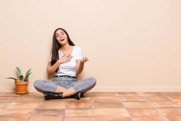 Jeune jolie femme se sentir heureuse et amoureuse, souriant d'une main à côté du cœur et de l'autre allongé à l'avant assis sur un sol