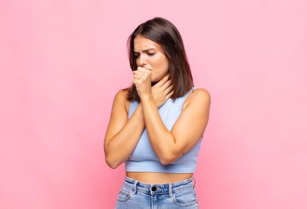 Jeune jolie femme se sentir malade avec un mal de gorge et des symptômes de grippe, tousser avec la bouche couverte