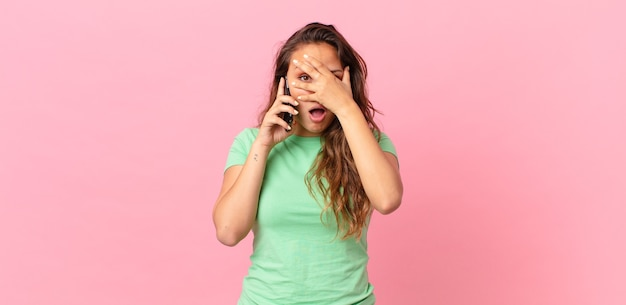 Jeune jolie femme semblant choquée, effrayée ou terrifiée, couvrant le visage avec la main et tenant un téléphone intelligent
