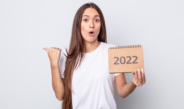 Jeune jolie femme semblant étonnée d'incrédulité. concept de planificateur 2022
