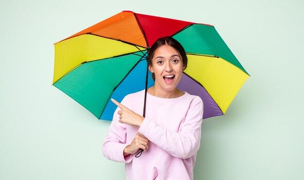 Jeune jolie femme semblant excitée et surprise en pointant sur le côté. concept de parapluie