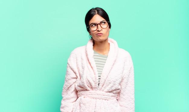 Jeune jolie femme semblant perplexe et confuse, se demandant ou essayant de résoudre un problème ou de penser. concept de pyjama