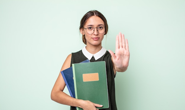 Jeune jolie femme semblant sérieuse montrant la paume ouverte faisant un geste d'arrêt. concept universitaire
