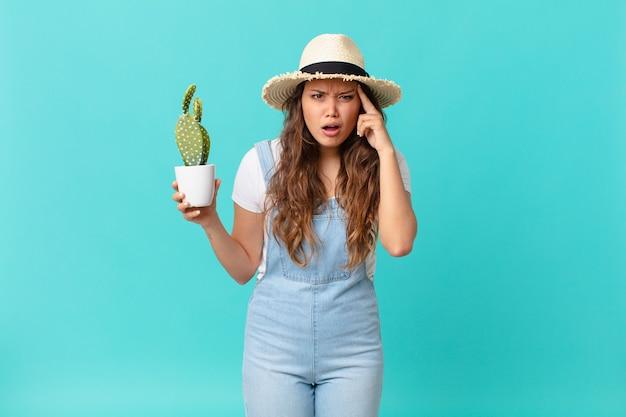 Jeune jolie femme semblant surprise, réalisant une nouvelle pensée, idée ou concept et tenant un cactus