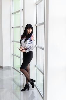 Jeune jolie femme sérieuse debout près de la fenêtre dans un bureau, tenant un cahier, regardant par la fenêtre.