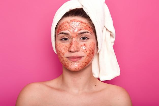 Jeune jolie femme avec une serviette blanche sur la tête, a un corps nu, souriant isolé sur un mur rose en studio, regarde directement la caméra, ayant un gommage rouge sur son visage.