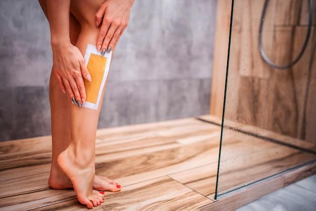 Jeune jolie femme sexy dans la douche. corps nu. vue en coupe des mains du modèle faisant l'épilation sur la jambe. soins auto-administrés. corps sportif. femme bien construite et mince.