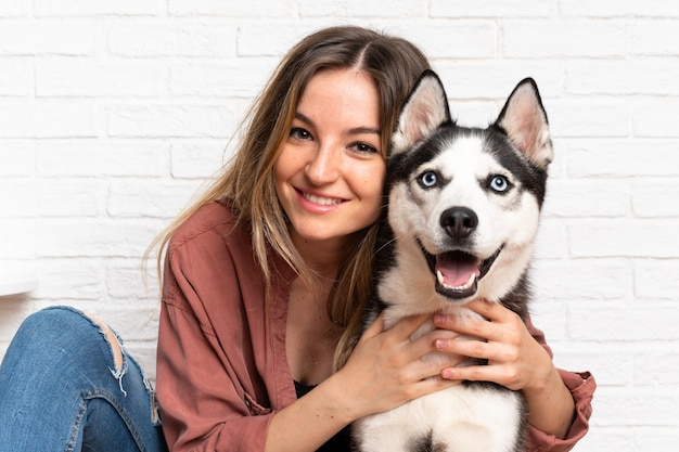 Jeune jolie femme avec son chien husky assis dans le sol à l'intérieur