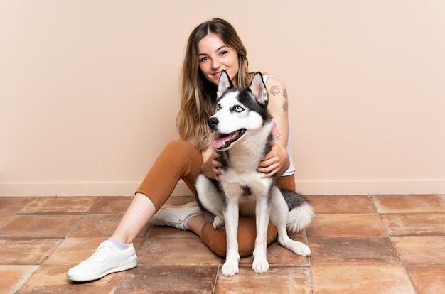 Jeune jolie femme avec son chien husky assis sur le sol à l'intérieur